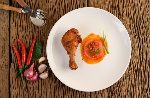 Gebratene hähnchenschenkel auf einem weißen teller mit sauce und knoblauch, schalotte, chili. Kostenlose Fotos