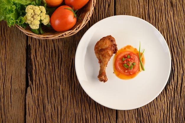 Gebratene hähnchenschenkel auf einem weißen teller mit sauce. Kostenlose Fotos
