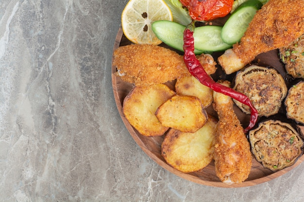 Gebratene hähnchenschenkel mit kartoffel und aubergine auf holzbrett. Kostenlose Fotos