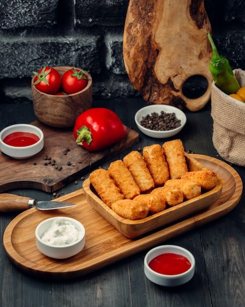Gebratene hähnchensticks auf einem holzbrett mit mayonnaise und tomatensauce. Kostenlose Fotos