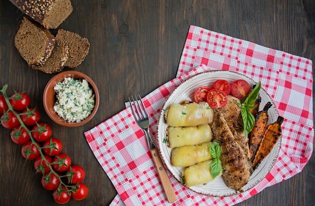 Gebratene hühnerbrust in verschiedenen variationen mit kirschtomaten, gemüse, paprikaröllchen Premium Fotos