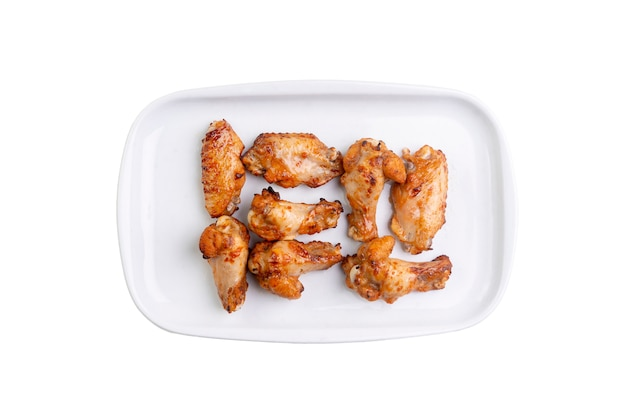 Gebratene hühnerflügel auf weißem teller isoliert. Premium Fotos