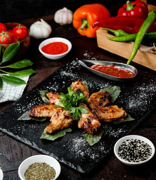 Gebratene hühnerflügel mit sauce in schwarzen gerichten Kostenlose Fotos