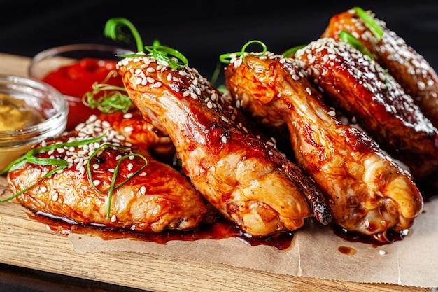 Gebratene hühnerflügel mit tomatensauce Premium Fotos