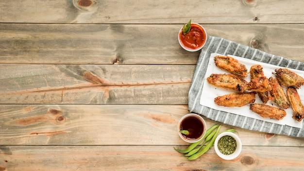 Gebratene hühnerflügel mit verschiedenen pikanten saucen Kostenlose Fotos