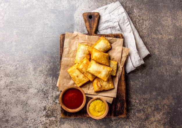 Gebratene käse empanadas. traditioneller lateinamerikanischer snack serviert auf holzbrett mit chili-sauce und senf. Premium Fotos