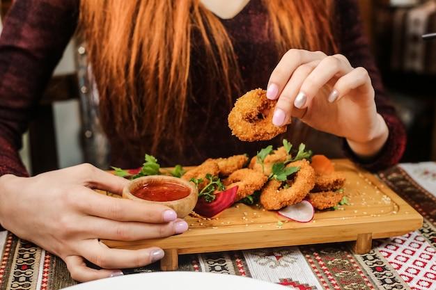 Gebratene kalamaryringe mit radieschen, petersilie, sesam und süßer chilisauce Kostenlose Fotos