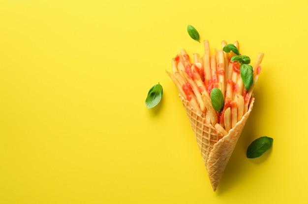 Gebratene kartoffeln in den waffelkegeln auf gelbem hintergrund. heiße salzige pommes frites mit soße, basilikumblätter. fast food, junk food, diät-konzept. Premium Fotos