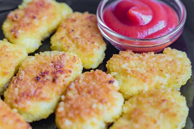 Gebratene knusperige hühnernuggets mit ketschup auf einem schwarzblech Premium Fotos