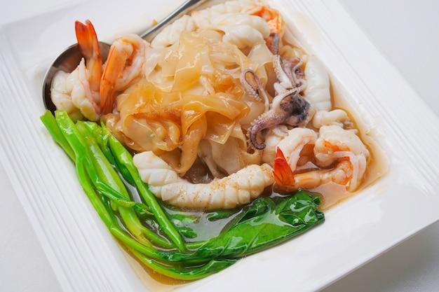 Gebratene nudel mit meeresfrüchten und kohl in der soße Premium Fotos
