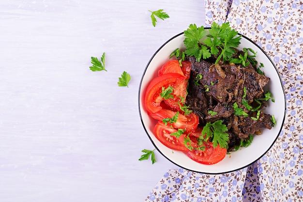Gebratene oder gegrillte rinderleber mit zwiebel- und tomatensalat, nahöstliche küche, draufsicht Premium Fotos