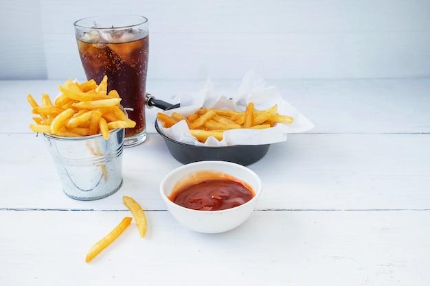 Gebratene pommes-frites und ketschup mit alkoholfreien getränken auf einer tabelle Premium Fotos