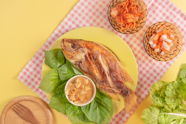Gebratener fisch auf einem teller mit gemüse serviert Premium Fotos