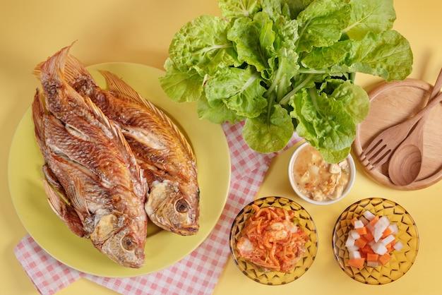 Gebratener fisch auf teller serviert eingelegtes gemüse und frische grüne blätter Premium Fotos