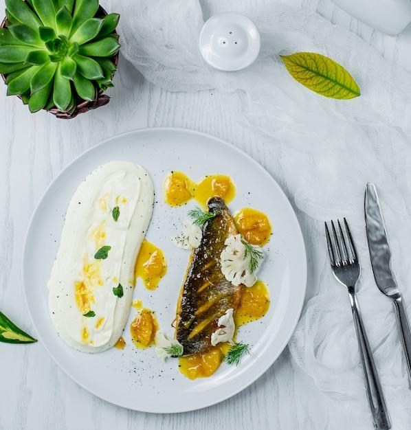 Gebratener fisch mit sauce in der platte Kostenlose Fotos