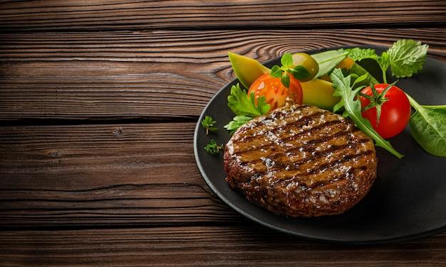Gebratener frischer großer rindfleischburger mit salat und kräutern auf schwarzem teller auf holztisch Premium Fotos