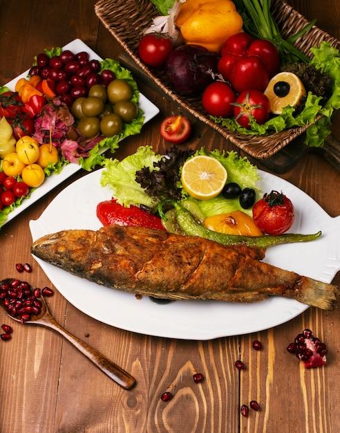 Gebratener gebratener ganzer fisch mit gegrilltem gemüse und salat. in weißen teller mit turshu auf holztisch dekoriert Kostenlose Fotos