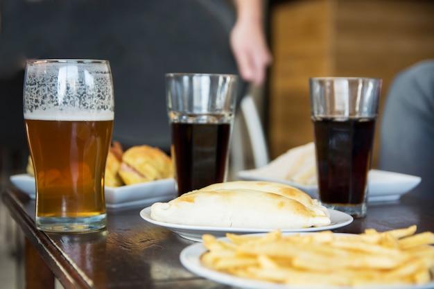 Gebratener imbiss mit alkoholischen getränken auf tabelle in der bar Kostenlose Fotos