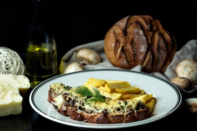 Gebratener pilz mit geschmolzenem käse überbacken auf braunem toast, dazu pommes Kostenlose Fotos