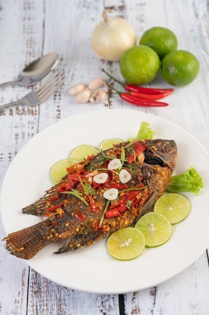 Gebratener tilapia mit chilisauce, zitronensalat und knoblauch auf einem teller auf einem weißen holztisch. Kostenlose Fotos