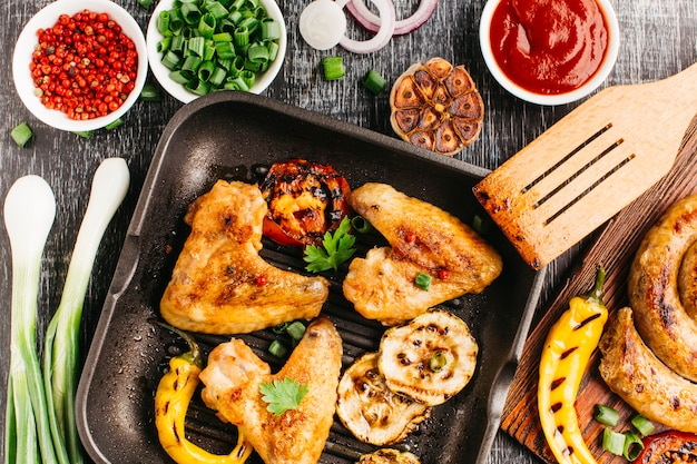 Gebratenes fleisch mit gemüse- und spiralwurst auf hölzernem schreibtisch Kostenlose Fotos