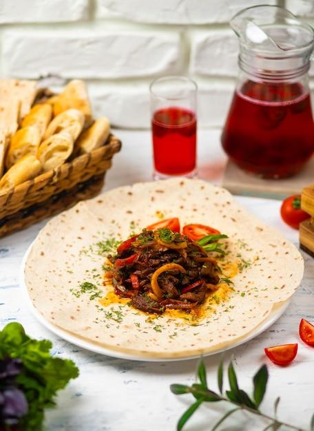 Gebratenes fleisch und gemüse mit kräutern auf einer weißen platte mit brotgemüse und glas wein Kostenlose Fotos