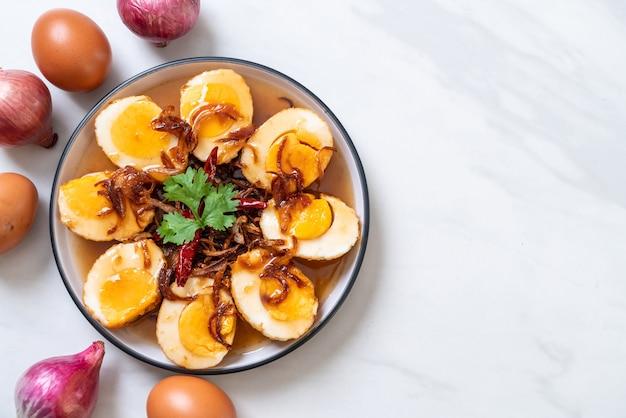Gebratenes gekochtes ei mit tamarindensauce oder süß-sauren eiern Premium Fotos