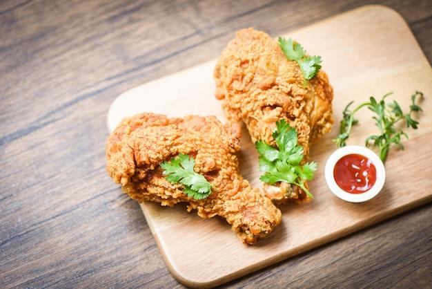 Gebratenes hühnerknusperig auf hölzernem brett der platte mit ketschup auf speisetische Premium Fotos