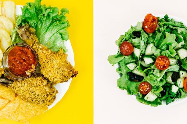 Gebratenes huhn der draufsicht gegen salat Kostenlose Fotos