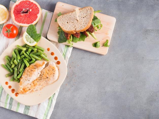 Gebratenes huhn mit grünen bohnen und sandwich auf dem tisch Kostenlose Fotos