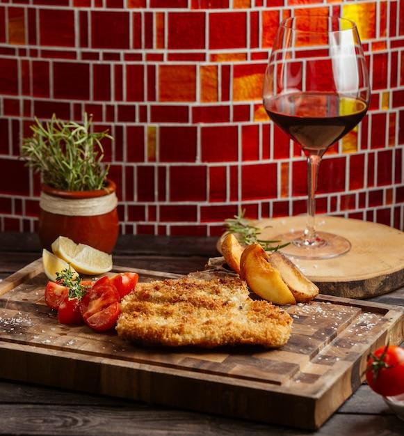 Gebratenes knuspriges huhn serviert mit tomaten und bratkartoffeln auf holzbrett Kostenlose Fotos