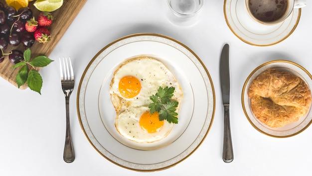 Gebratenes omelett mit brot und früchten frühstücken über dem weißen hintergrund Premium Fotos