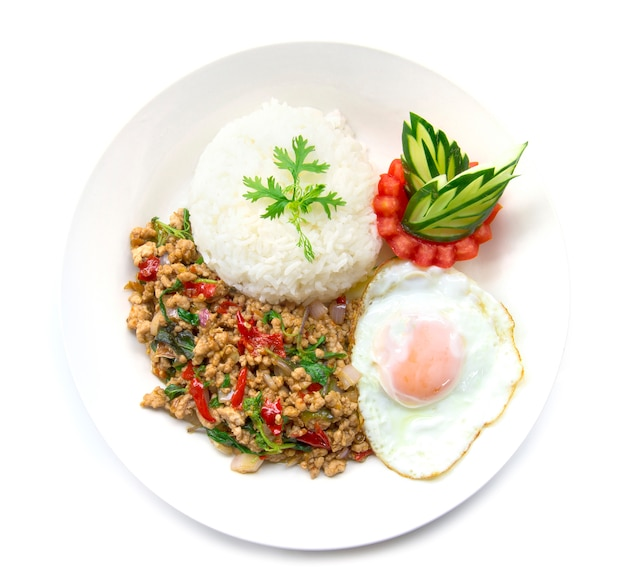 Gebratenes schweinefleisch des thailändischen lebensmittels würzig und basilikum diente mit reis und spiegelei und tomatengurke Premium Fotos