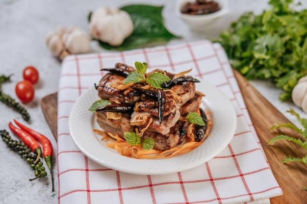 Gebratenes schweinefleisch mit gebratenem chili gebratene zwiebel und minze in einem weißen teller. Kostenlose Fotos