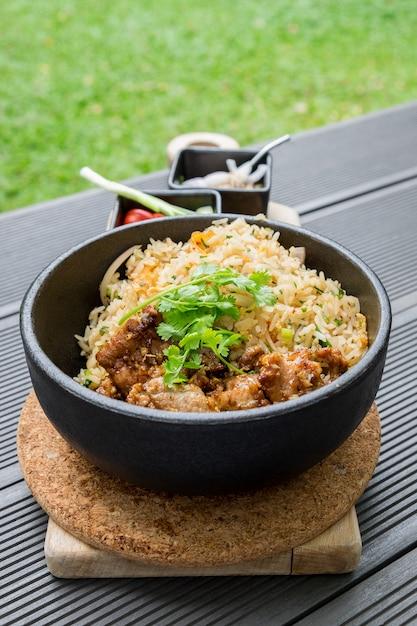 Gebratenes schweinefleisch mit knoblauchgemüse mit der würzigen und sauren thailändischen nahrung der soße köstlich im schwarzblech Premium Fotos