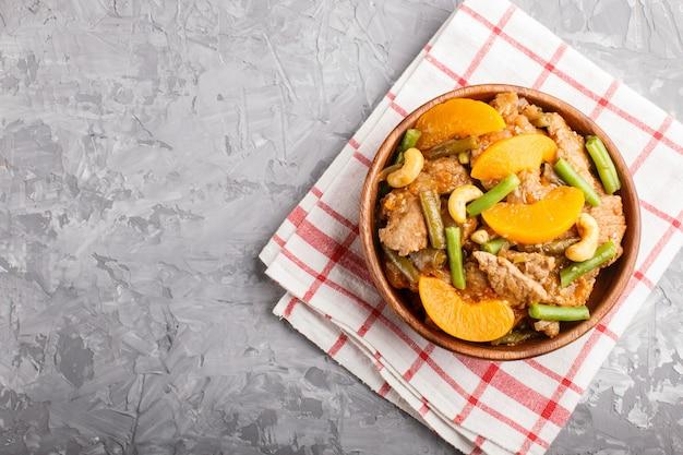 Gebratenes schweinefleisch mit pfirsichen, acajoubaum und grünen bohnen in einer hölzernen schüssel auf einem grauen konkreten hintergrund, kopienraum. Premium Fotos