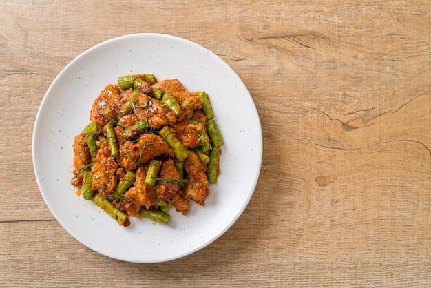 Gebratenes schweinefleisch und rote curry-paste mit stachelbohnen nach asiatischer art umrühren Premium Fotos