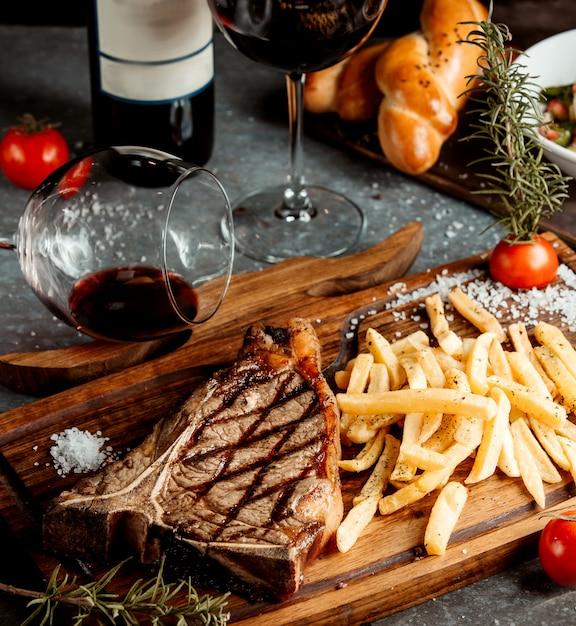 Gebratenes steak mit pommes frites auf holzbrett Kostenlose Fotos