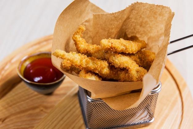 Gebratenes stück huhn im metallkorb auf holztisch in einem restaurant. fast food Premium Fotos