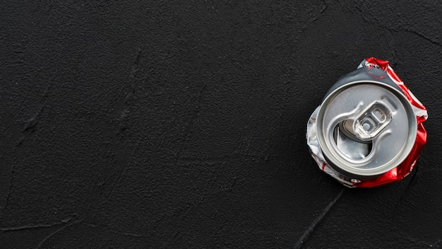 Gebrauchte abgeflachte dose auf schwarzem hintergrund platziert Kostenlose Fotos