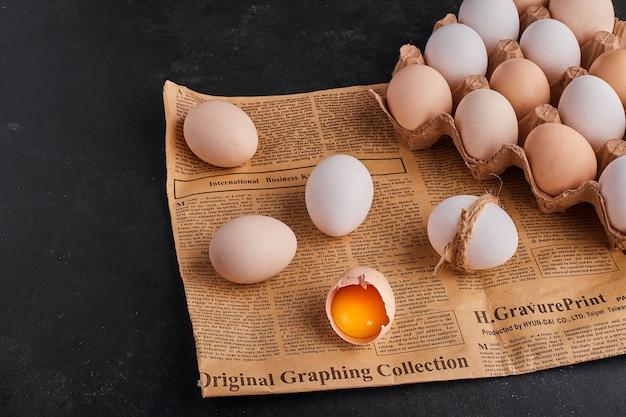 Gebrochene eier auf einem stück zeitung und auf einem pappbehälter. Kostenlose Fotos