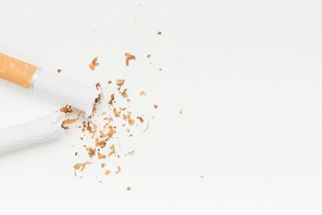 Gebrochene zigarette und tabak über weißem hintergrund Kostenlose Fotos