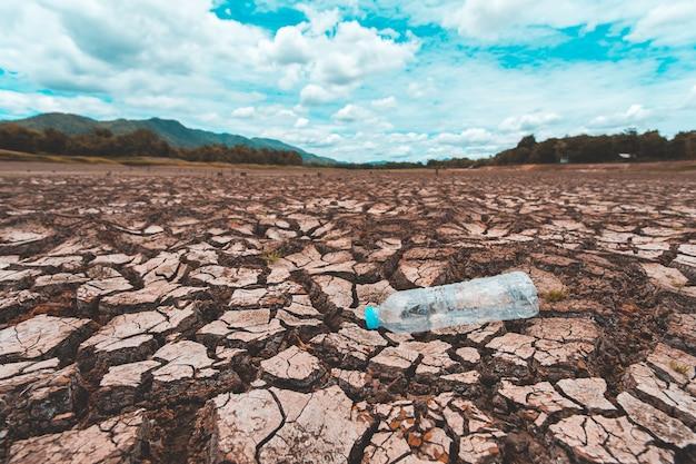 Gebrochenes trockenes land mit leerer plastikflasche Premium Fotos