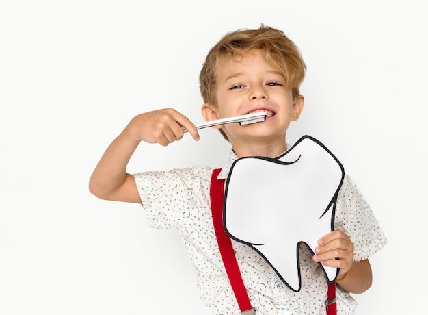 Gebürstete zähne des kleinen jungen, die papercraft-zahn halten Premium Fotos