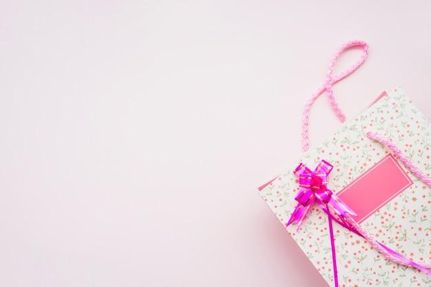 Geburtstags-einkaufstasche mit rosa bogen auf rosa hintergrund Kostenlose Fotos