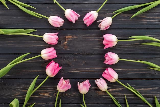 Geburtstags- oder hochzeitsmodell mit rosa tulpe blüht auf draufsicht des hölzernen hintergrundes. Premium Fotos