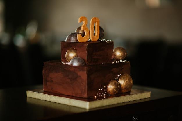 Geburtstagschokoladenkuchen mit einer zahl dreißig. verziert mit goldenen schokoladenkugeln. alles gute zum geburtstag Premium Fotos