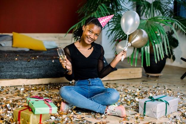 Geburtstagsfeier, neujahrskarneval. junge afrikanische lächelnde frau, die helles ereignis feiert ,. funkelndes konfetti, spaß haben, tanzen und champagner trinken Premium Fotos