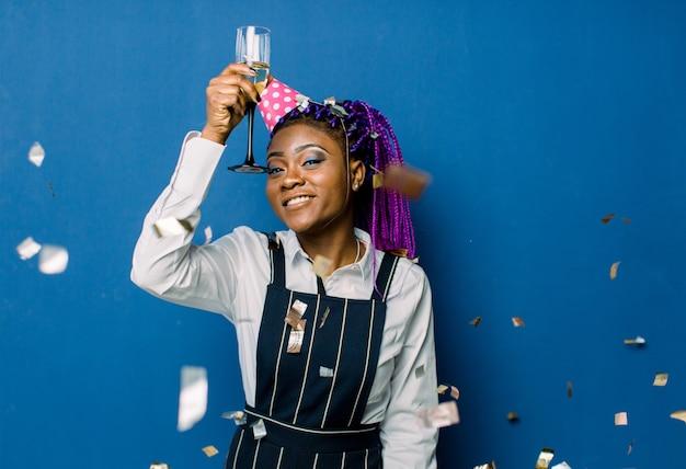 Geburtstagsfeier, neujahrskarneval. junge lächelnde afrikanische frau auf blauem raum, der helles ereignis feiert, trägt elegante modekleidung und rosa partyhut. funkelndes konfetti, spaß haben, tanzen Premium Fotos