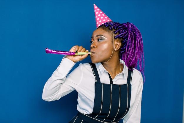 Geburtstagsfeier, neujahrskarneval. junge lächelnde afrikanische frau auf blauem raum, der helles ereignis feiert, trägt eleganten weißen moderock und schwarze hose, mit rosa partyhut mit krachmacher. Premium Fotos